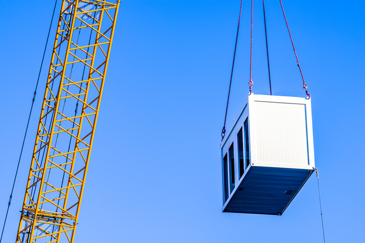 mobile office at a crane in front of blue sky