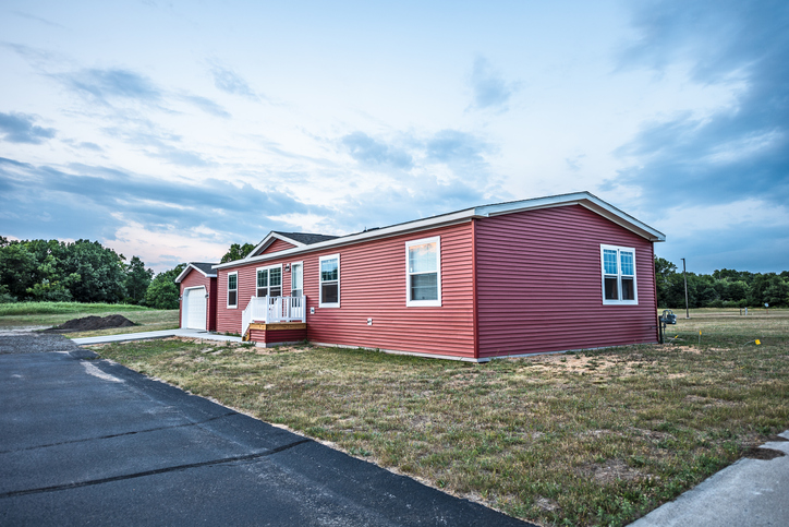 New manufactured home in a new community. The window on the far right on the front shows a reflection of the sunset at the top.