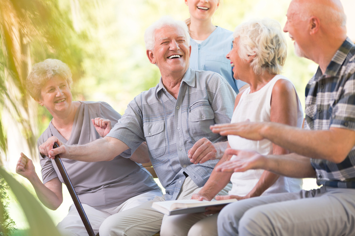 Group of smiling senior friends enjoying time while sitting together in park