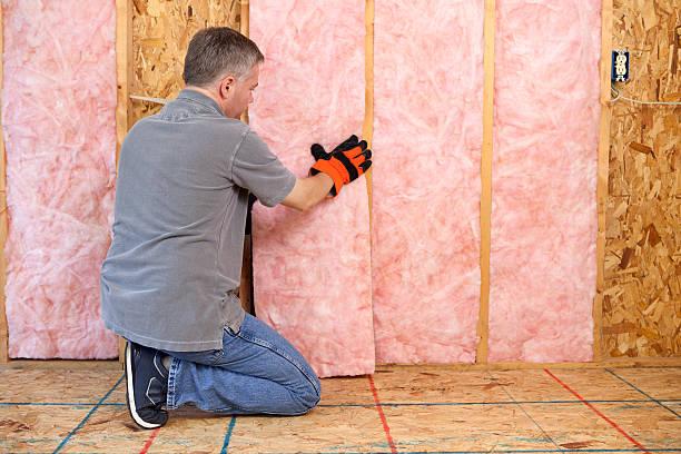 Man installing fiberglass insulation in the wall.